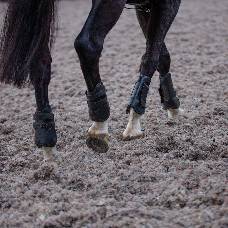 Horses hooves on Canter Carpet equestrian surface in arena